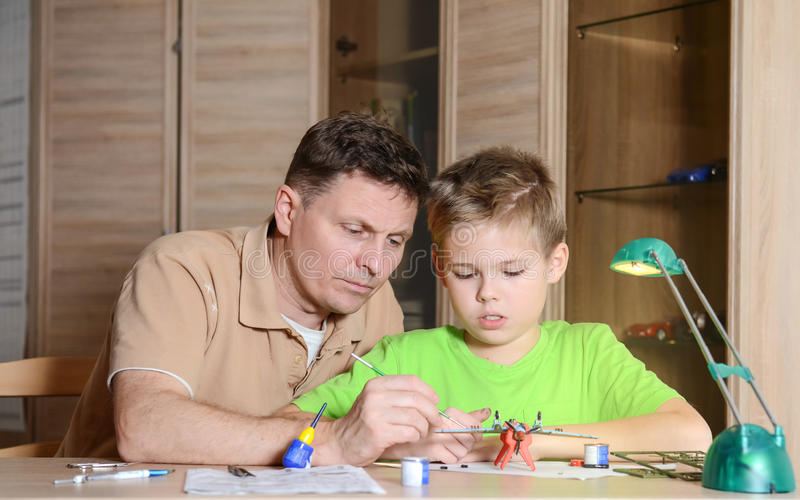 帮助他的有式样飞机的父亲儿子 人和男孩做航空器模型 免版税图库摄影