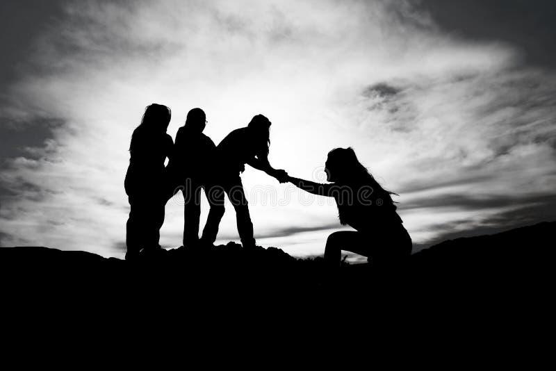 帮手剪影在两登山人之间的 免版税图库摄影
