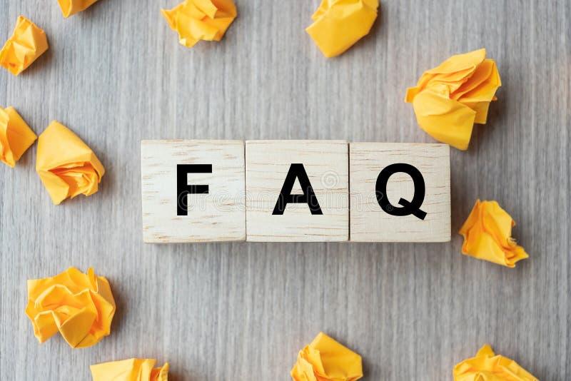 常见问题解答频率要求与木立方体块和黄色被粉碎的纸的问题词在桌背景 回答,问,要求, 库存图片