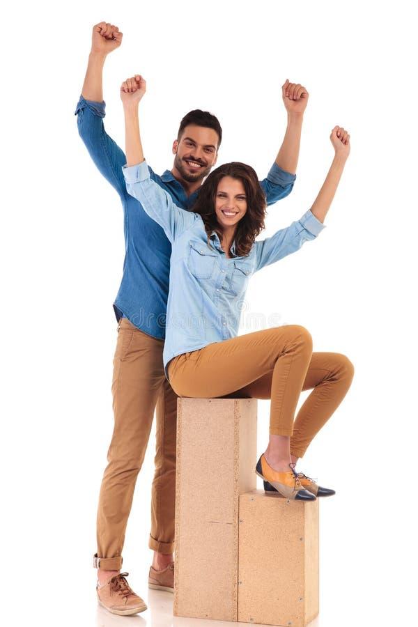 常设庆祝成功的男人和安装的偶然妇女 库存照片