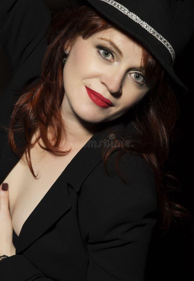 黑帽会议和夹克的美丽的妇女在黑暗的背景 库存图片