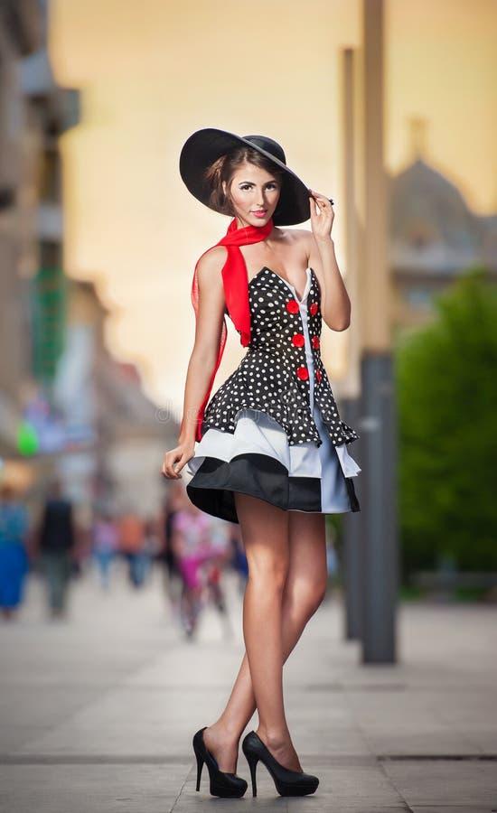 戴黑帽会议的时兴的夫人摆在街道上 免版税库存图片