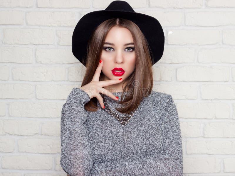 黑帽会议的有红色充分的嘴唇的,明亮的构成美丽的性感的女孩和绘红色我的钉子 免版税库存图片