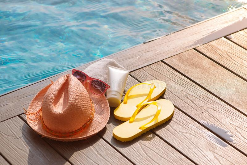 帽子、太阳镜和遮光剂在游泳池, summ的边 库存图片