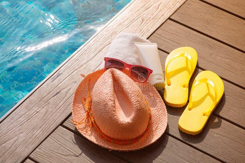 帽子、太阳镜和遮光剂在游泳池, summ的边 免版税库存图片
