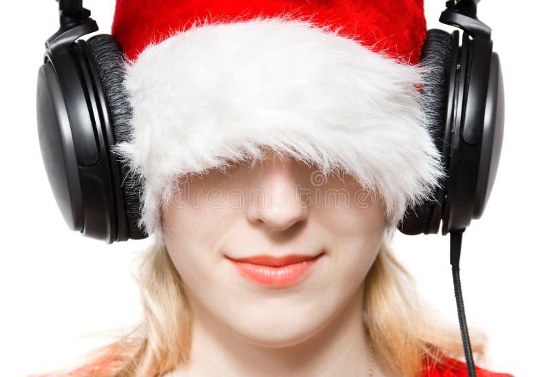 帽子听的音乐圣诞老人妇女 免版税库存照片