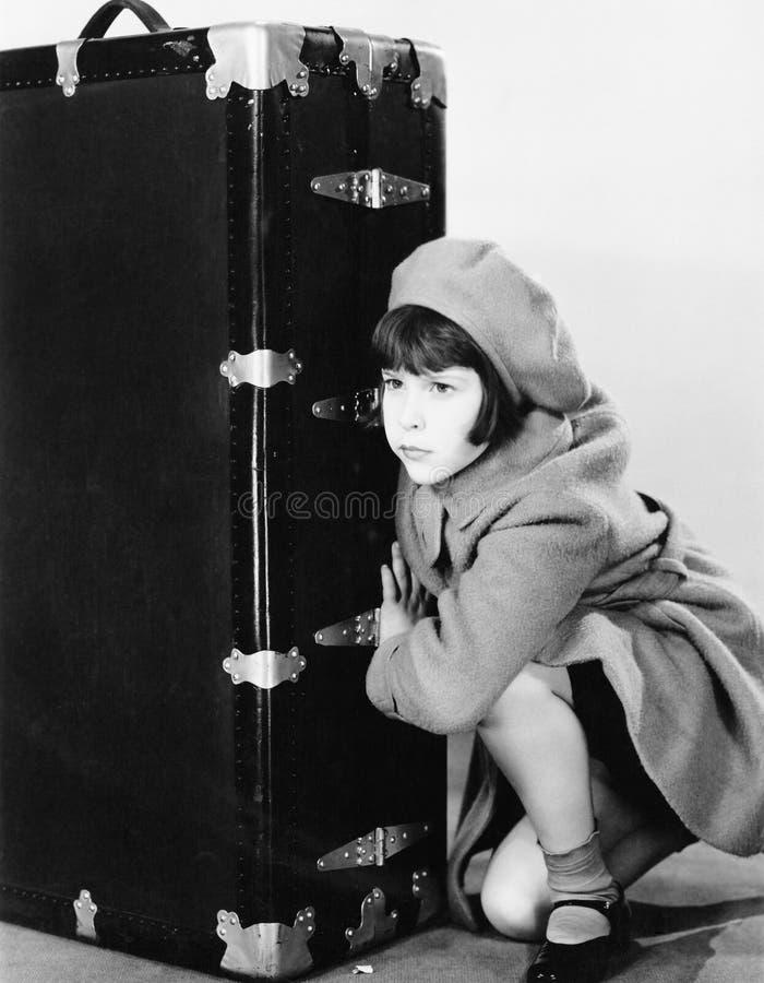 帽子和外套的小女孩蹲下在手提箱旁边的(所有人被描述不更长生存,并且庄园不存在 Suppli 库存照片