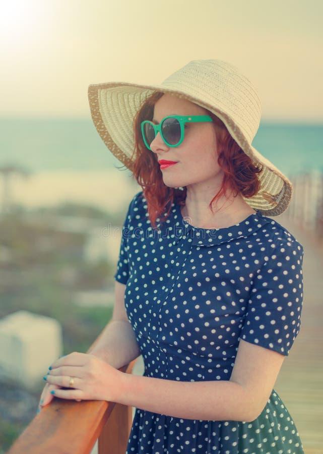 帽子和太阳镜的红发女孩 库存照片