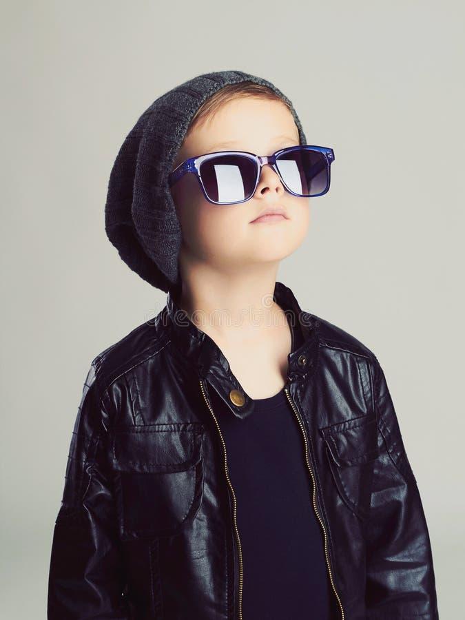 帽子和太阳镜的滑稽的孩子 红色礼服 图库摄影