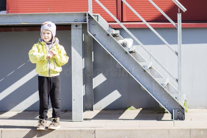 帽子和夹克的男孩在金属楼梯调查附近距离 库存图片