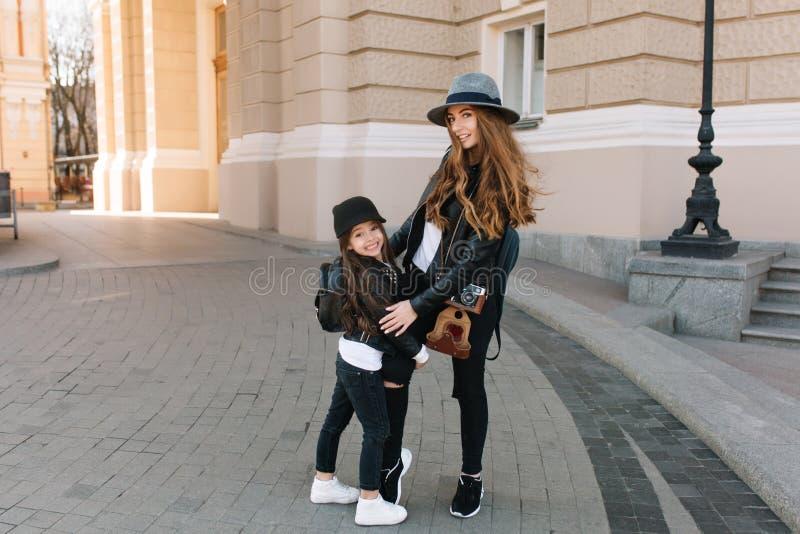 帽子和时髦的夹克的激动的深色的女孩接受她的母亲的腿身分的在街道中间 快乐好 库存照片