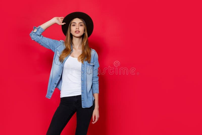帽子和牛仔布的前面画象年轻女人,看照相机,隔绝在红色背景,与拷贝空间 库存图片