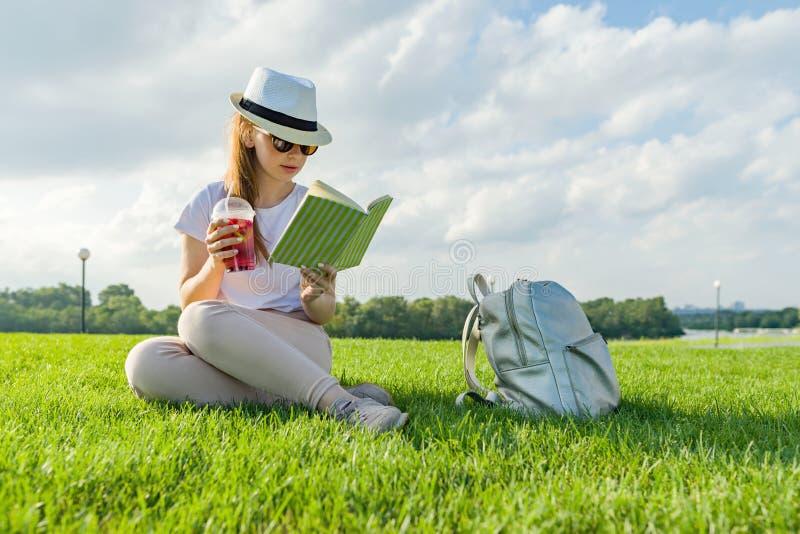 帽子和玻璃的年轻十几岁的女孩读书,喝凉快的莓果饮料 享受夏天坐在同水准的绿草 图库摄影