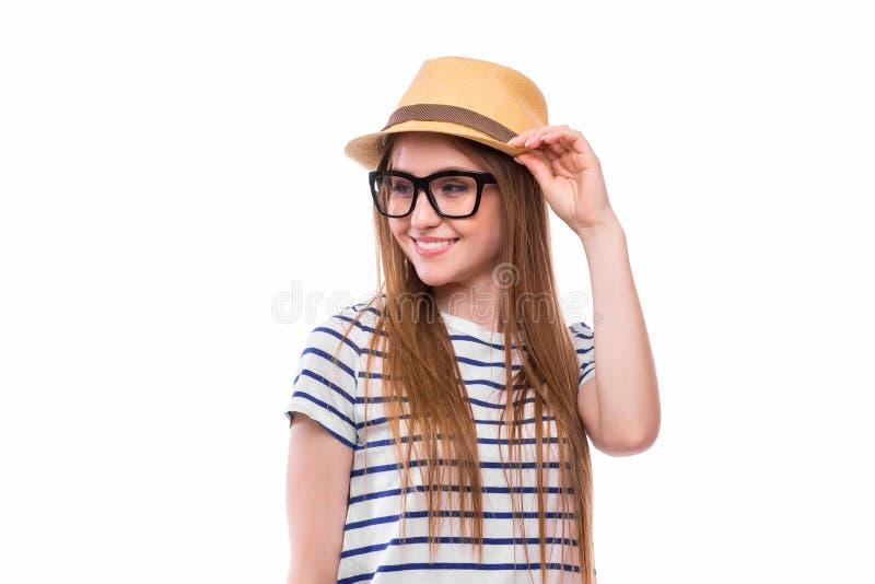 戴帽子和眼镜的年轻愉快的旅游女孩 免版税图库摄影