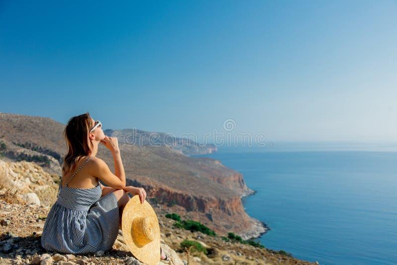 帽子和礼服的女孩有海海岸线的 免版税库存照片