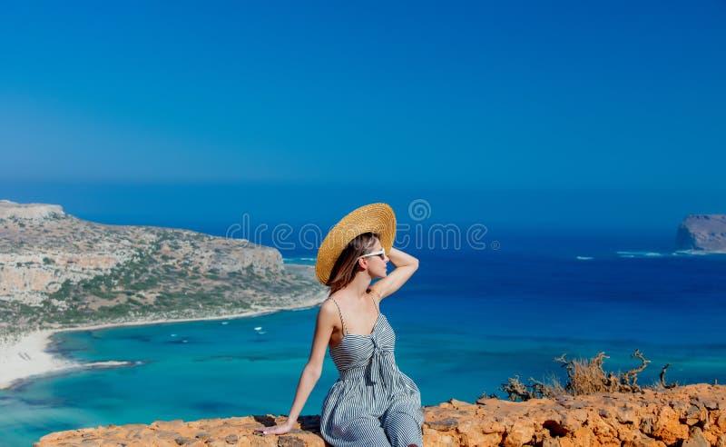 帽子和礼服的女孩有海海岸线的 免版税图库摄影