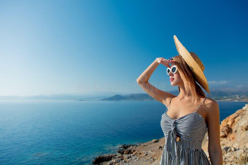 帽子和礼服的女孩有海海岸线的 免版税库存图片