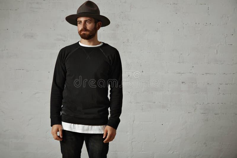 帽子和空白的黑衬衣的年轻有胡子的人 免版税库存照片