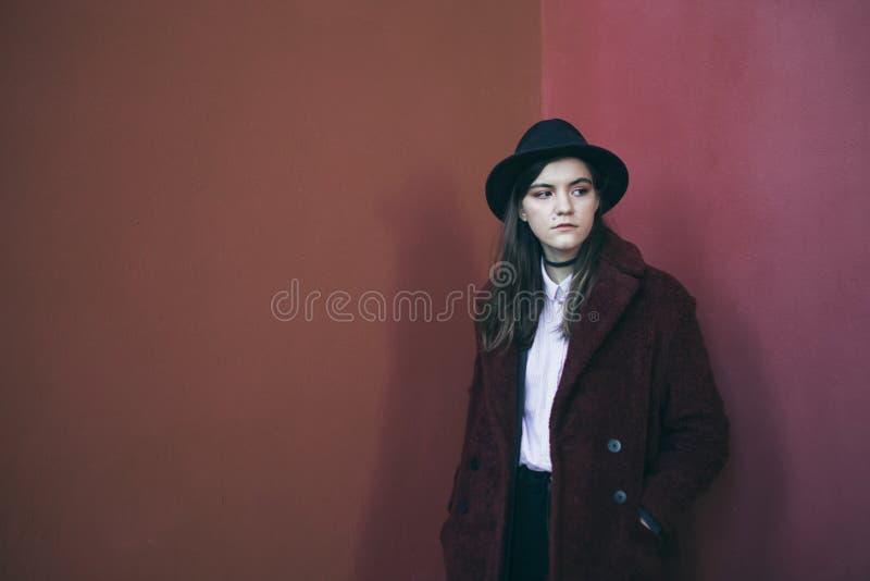 帽子和红色毛皮大衣的美丽的时髦的少年女孩 红色镇静悲伤心情 解决问题 时尚街道样式 库存图片