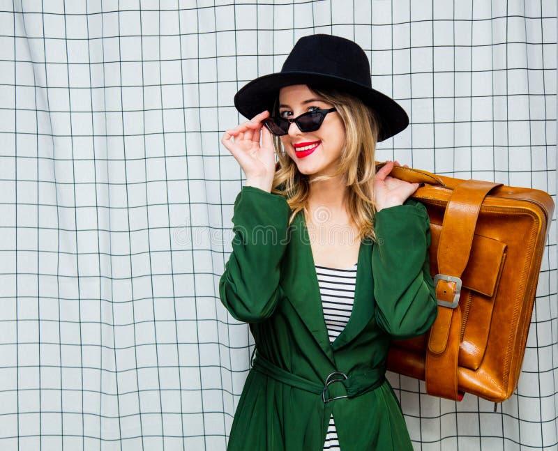 帽子和绿色斗篷的妇女在90s带着旅行手提箱的样式 免版税库存照片