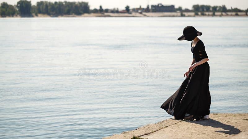 帽子和长的黑礼服跳舞的芭蕾舞女演员在河岸 库存图片