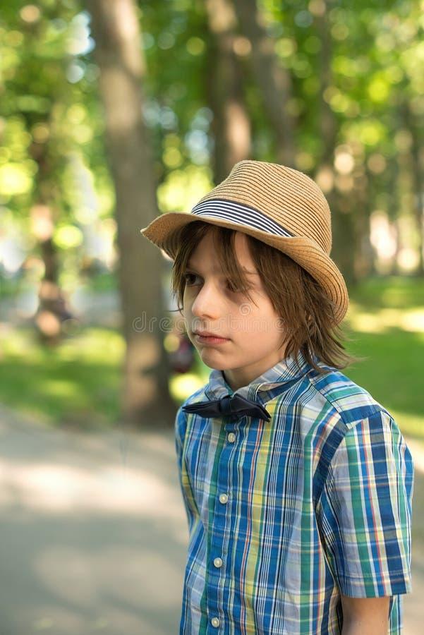 帽子和领带的男小学生-蝴蝶在公园去 H 库存图片