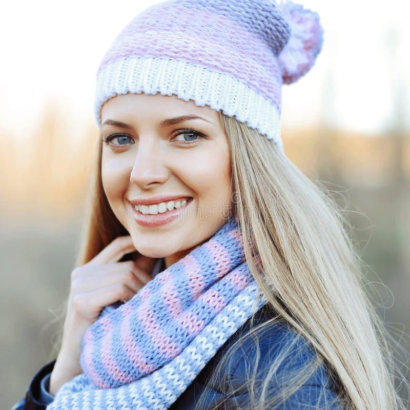 帽子和围巾的美丽的年轻肉欲的白肤金发的女孩在冷的wea 免版税库存照片
