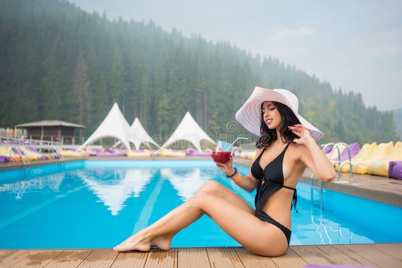 帽子和黑比基尼泳装的少妇在游泳池旁边和饮用的鸡尾酒坐森林背景  图库摄影