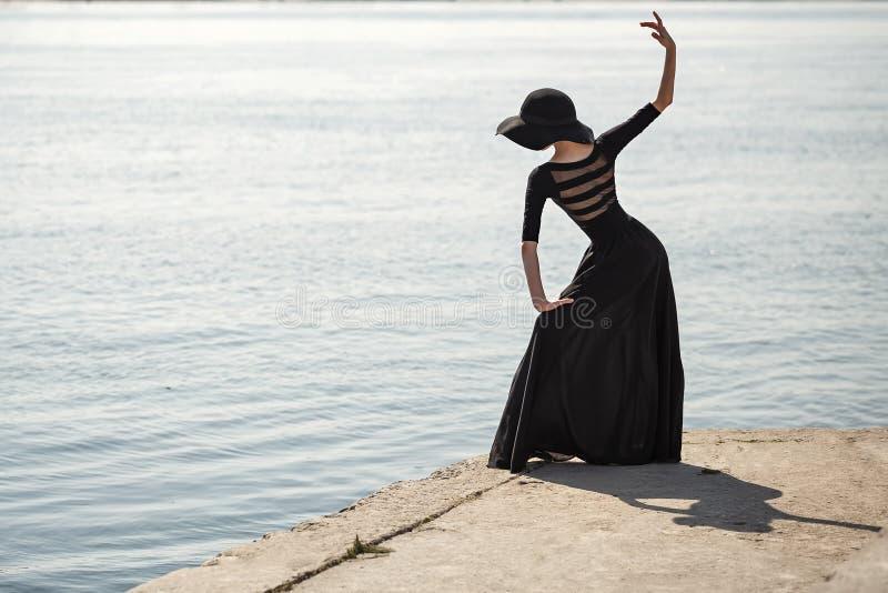 帽子和黑礼服跳舞的芭蕾舞女演员在街道 库存照片