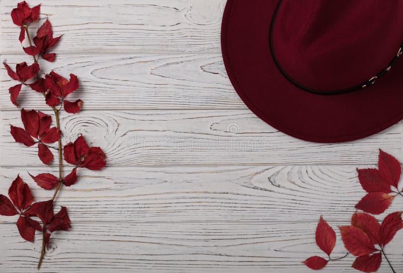 帽子在灰色木背景的伯根地颜色与秋天红色l 免版税库存照片