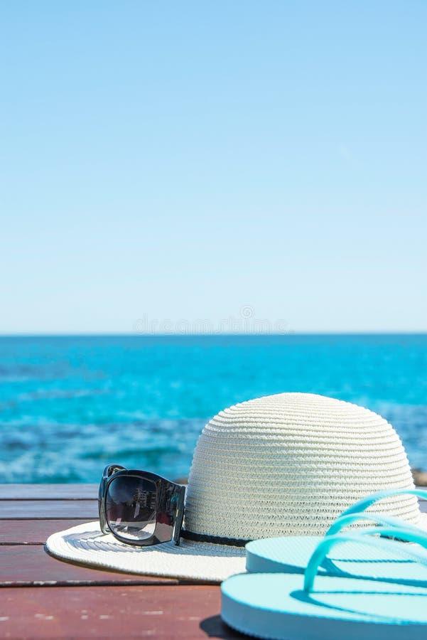 帽子在蓝天和绿松石海背景的太阳镜拖鞋 暑假旅行放松 田园诗海景视图 库存照片