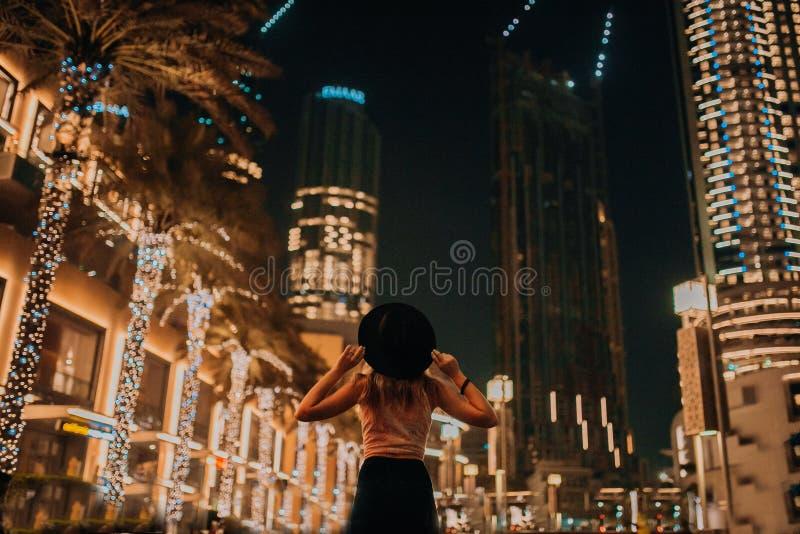 帽子时装的,残酷人,时髦的成套装备,在街道下的步行英俊的妇女 凉快的光和棕榈 免版税图库摄影