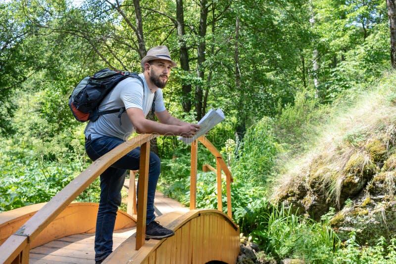 帽子的一个旅客有背包的在桥梁站立探索区域的,确定在地图的道路的年轻有胡子的人 库存图片