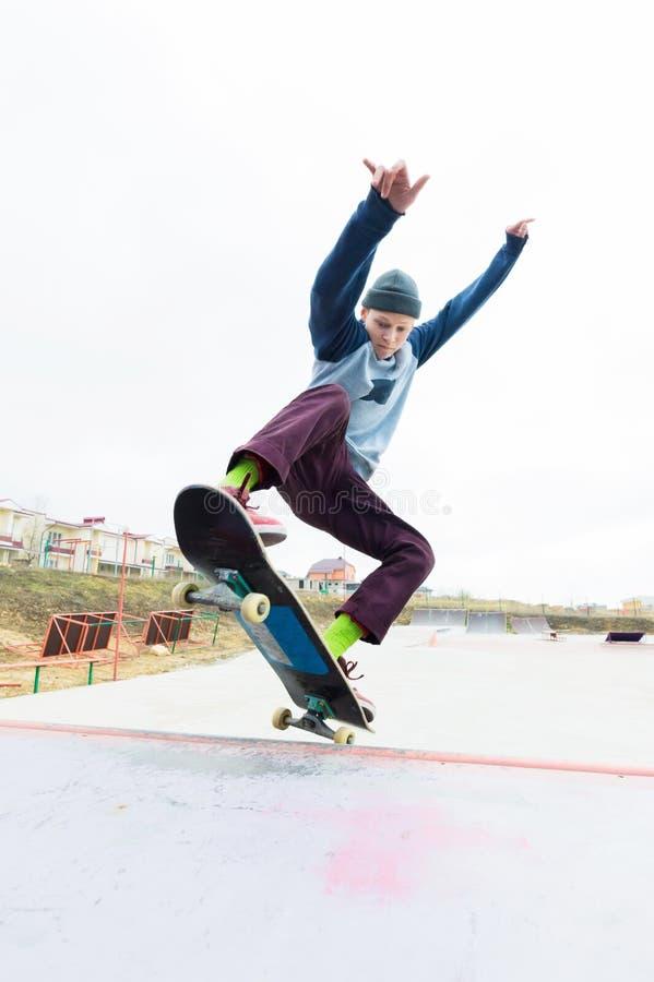 帽子的一个溜冰板者少年做与一个跃迁的一个把戏在舷梯 溜冰板者在天空中飞行 免版税库存照片