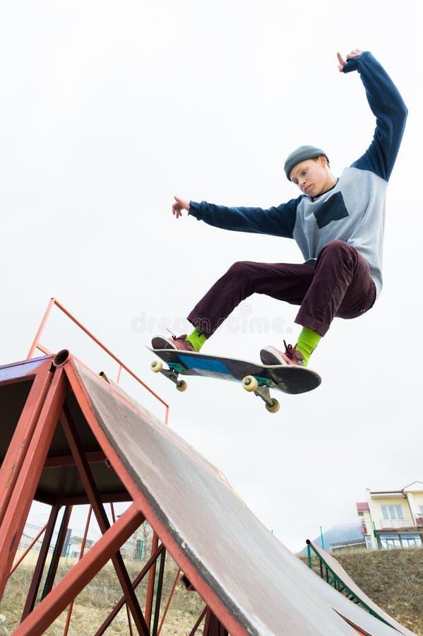 帽子的一个溜冰板者少年做与一个跃迁的一个把戏在舷梯 溜冰板者在天空中飞行 图库摄影