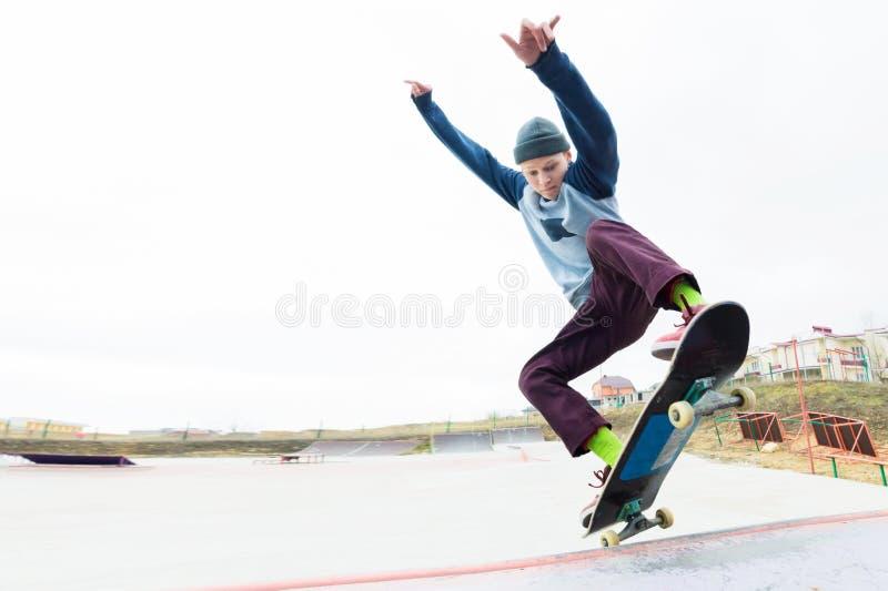 帽子的一个溜冰板者少年做与一个跃迁的一个把戏在舷梯 溜冰板者在天空中飞行 免版税图库摄影