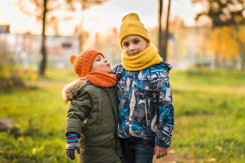 帽子的两个男孩互相拥抱 免版税库存照片