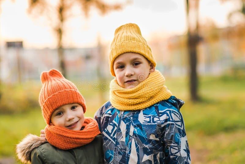 帽子的两个男孩互相拥抱 免版税库存图片