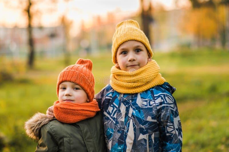 帽子的两个男孩互相拥抱 图库摄影