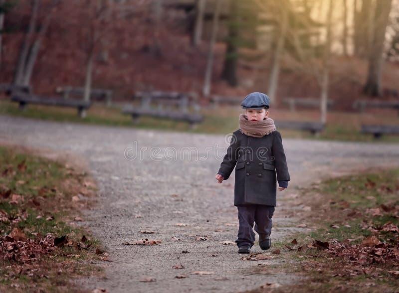 戴帽子的严肃的小男孩走在一条道路在一个公园在一冷颤的天 库存图片