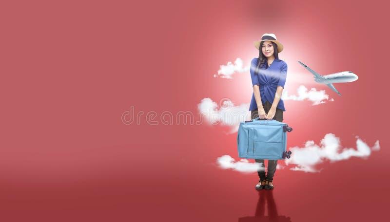 帽子的亚裔妇女有手提箱袋子去的旅行的与飞机 库存照片