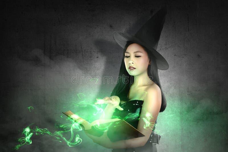 帽子的亚裔巫婆妇女学会从不可思议的书的咒语 库存照片