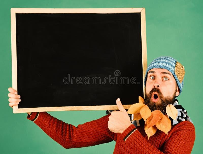帽子的人拿着在绿色背景的黑板 有震惊面孔和胡子的行家樱桃充分离开 库存照片