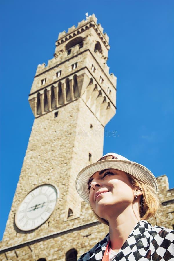 帽子的俏丽的妇女摆在c的Palazzo Vecchio下 库存图片