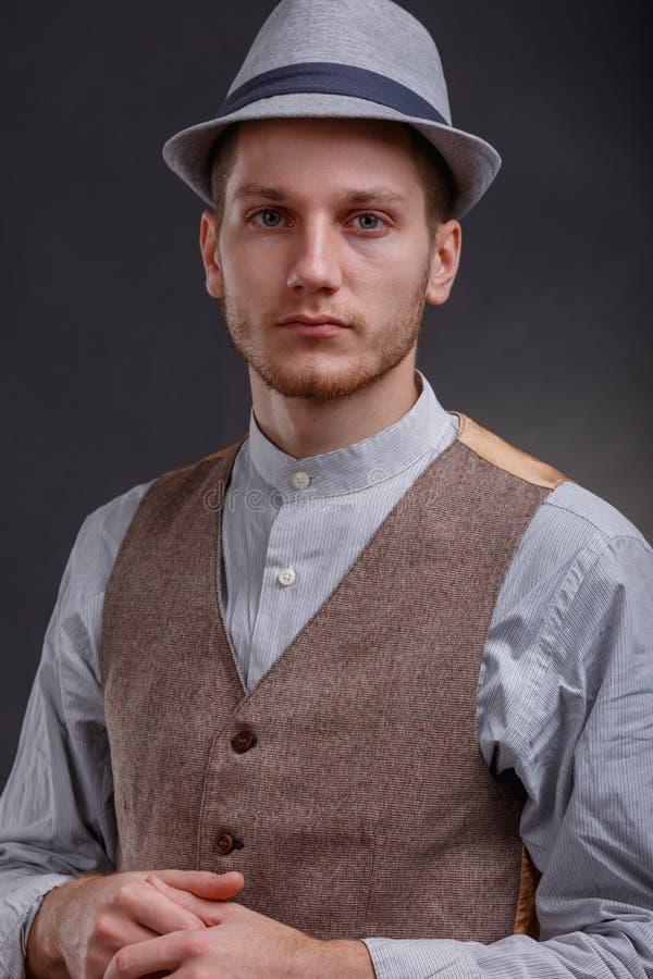 帽子的匪徒握他的在灰色背景的手 免版税图库摄影
