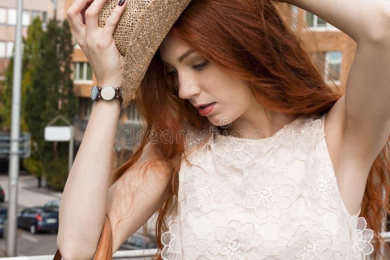 帽子的华美的妇女在多云天空 免版税库存照片
