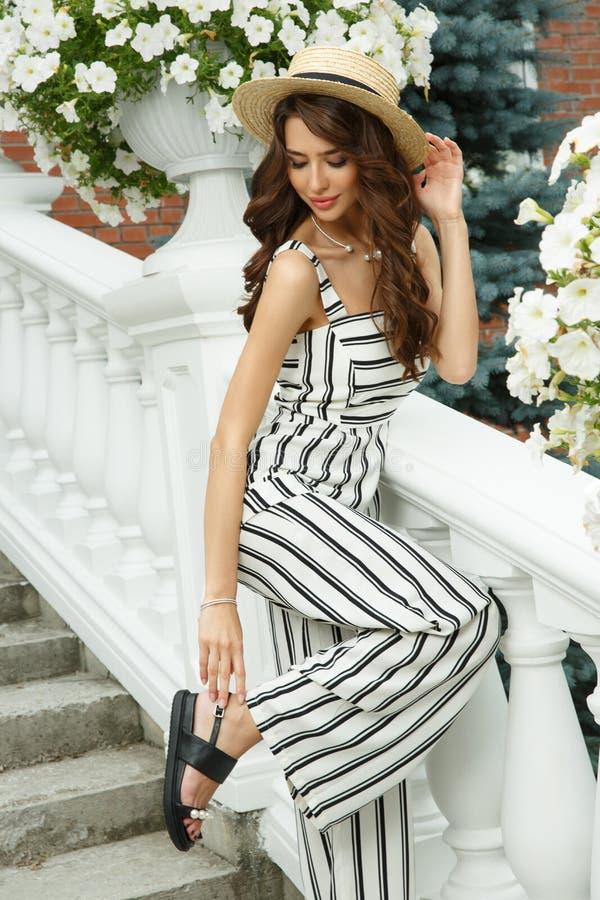 帽子的可爱和典雅的富有的小姐在美丽的豪宅台阶摆在  免版税库存照片