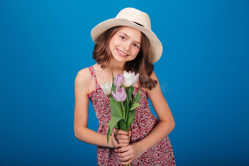帽子的可爱的微笑的小女孩有花花束的  免版税库存图片