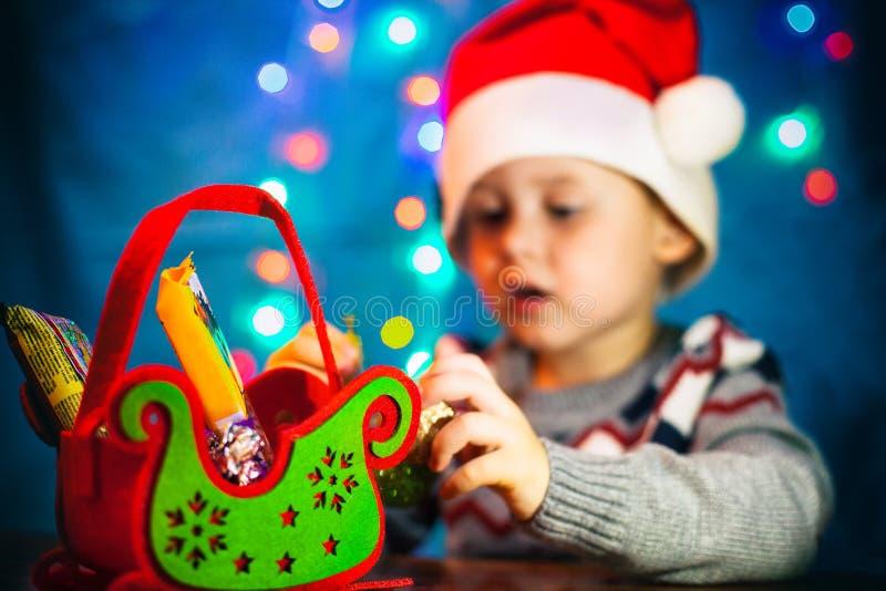 帽子的圣诞老人一个逗人喜爱的男孩看一件礼物 糖果圣诞节雪橇 有圣诞老人帽子的小逗人喜爱的男孩 免版税库存照片