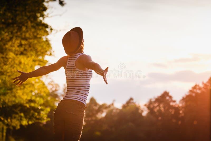 帽子的女孩享受自然的 免版税库存图片